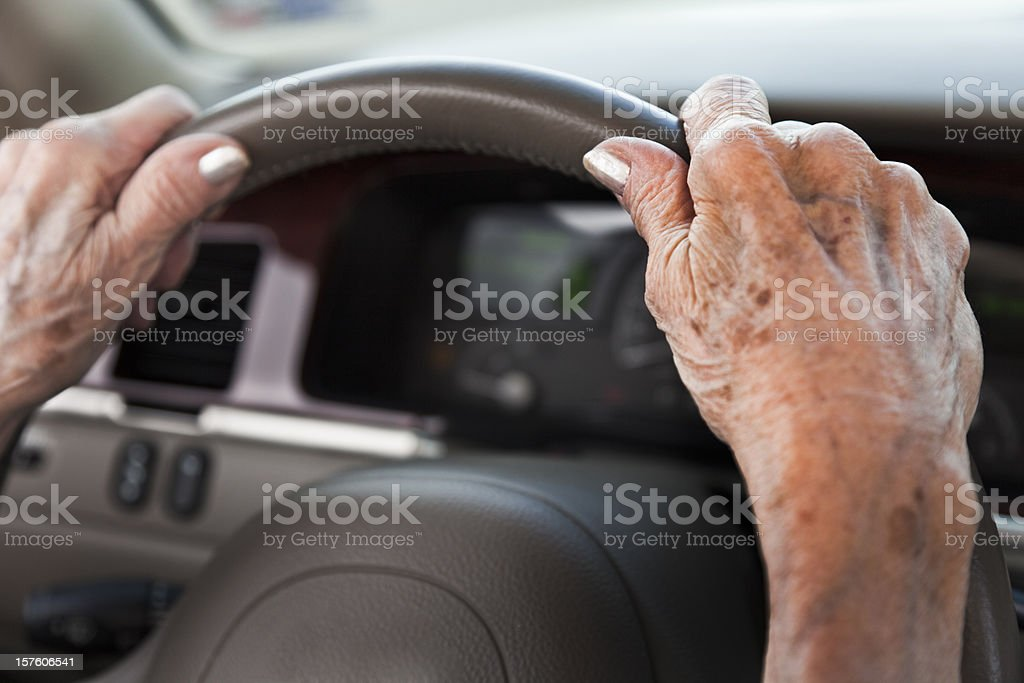 senior woman hands, driving car, steering wheel stock photo