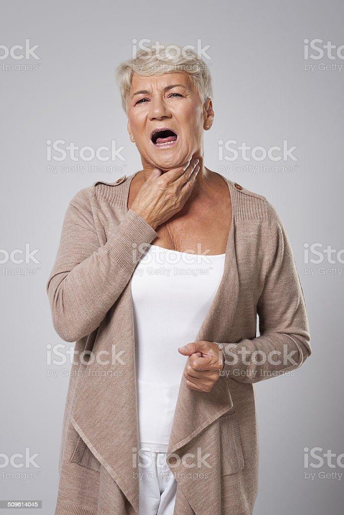 Senior woman has big problems with sore throat stock photo