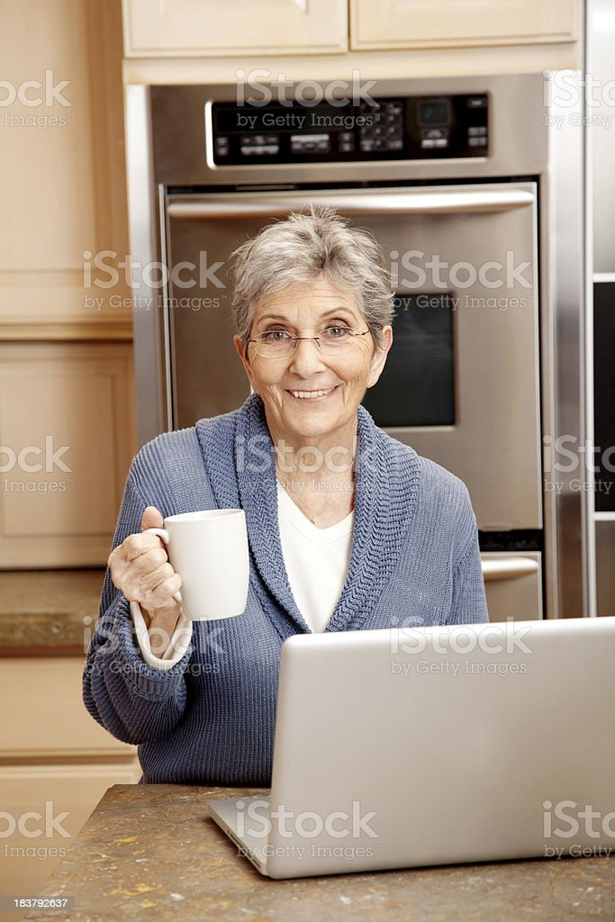 Senior Woman Having a Cup of Coffee in Kitchen royalty-free stock photo