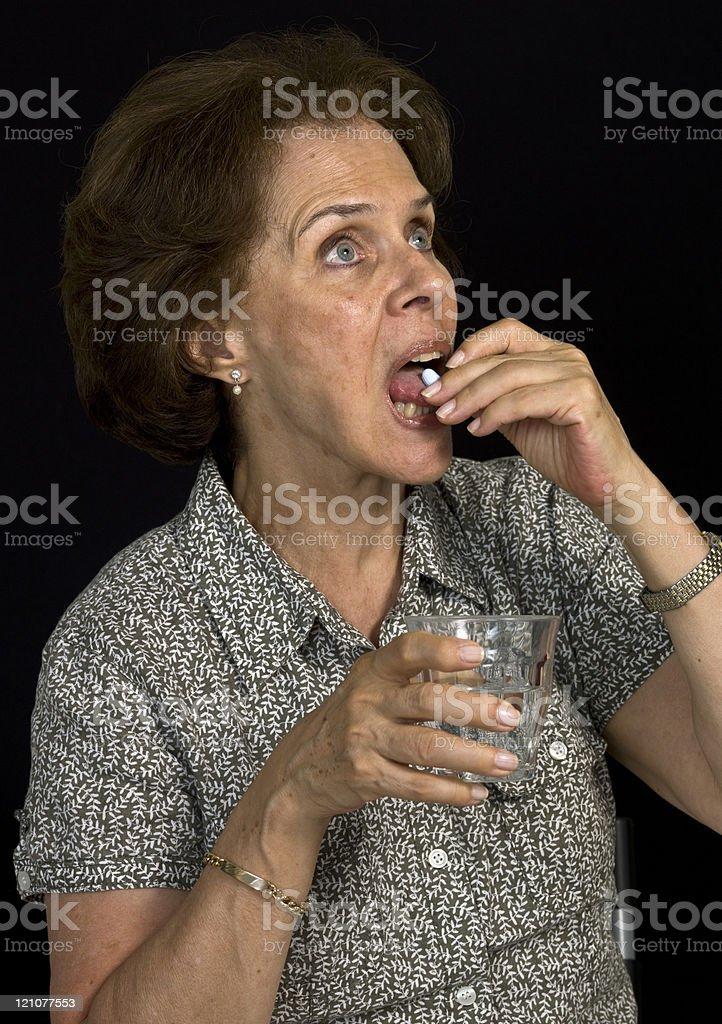 Senior woman having a pill stock photo