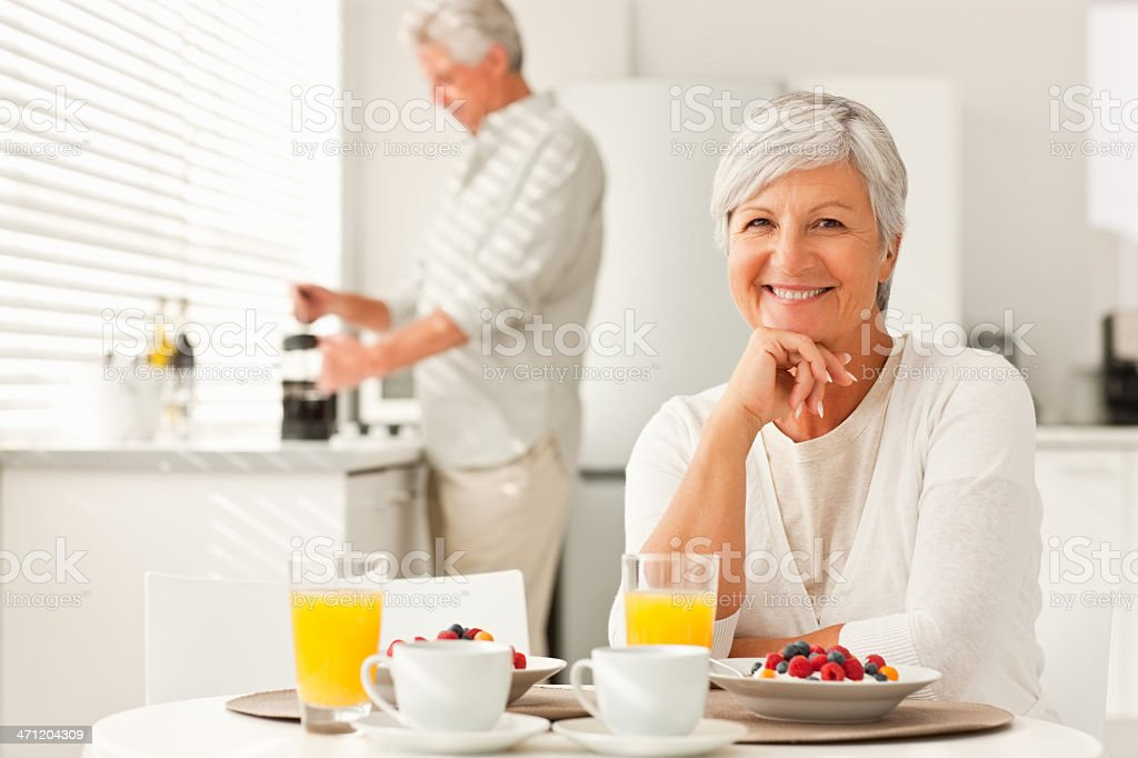 Senior woman having breakfast with husband at the back royalty-free stock photo