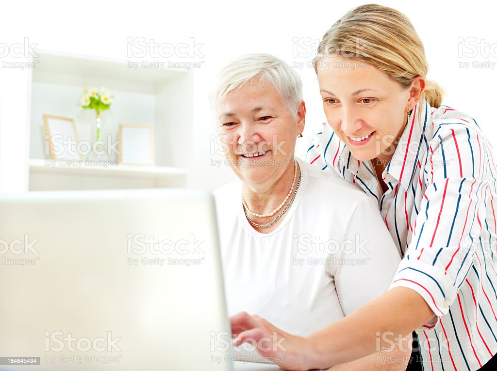 Senior Woman Having Fun on laptop with her adult daughter royalty-free stock photo