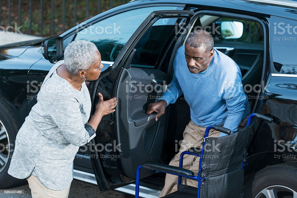 Senior woman helping disabled husband out of car stock photo