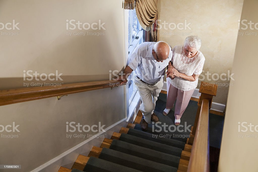 Senior woman helping husband climb staircase stock photo
