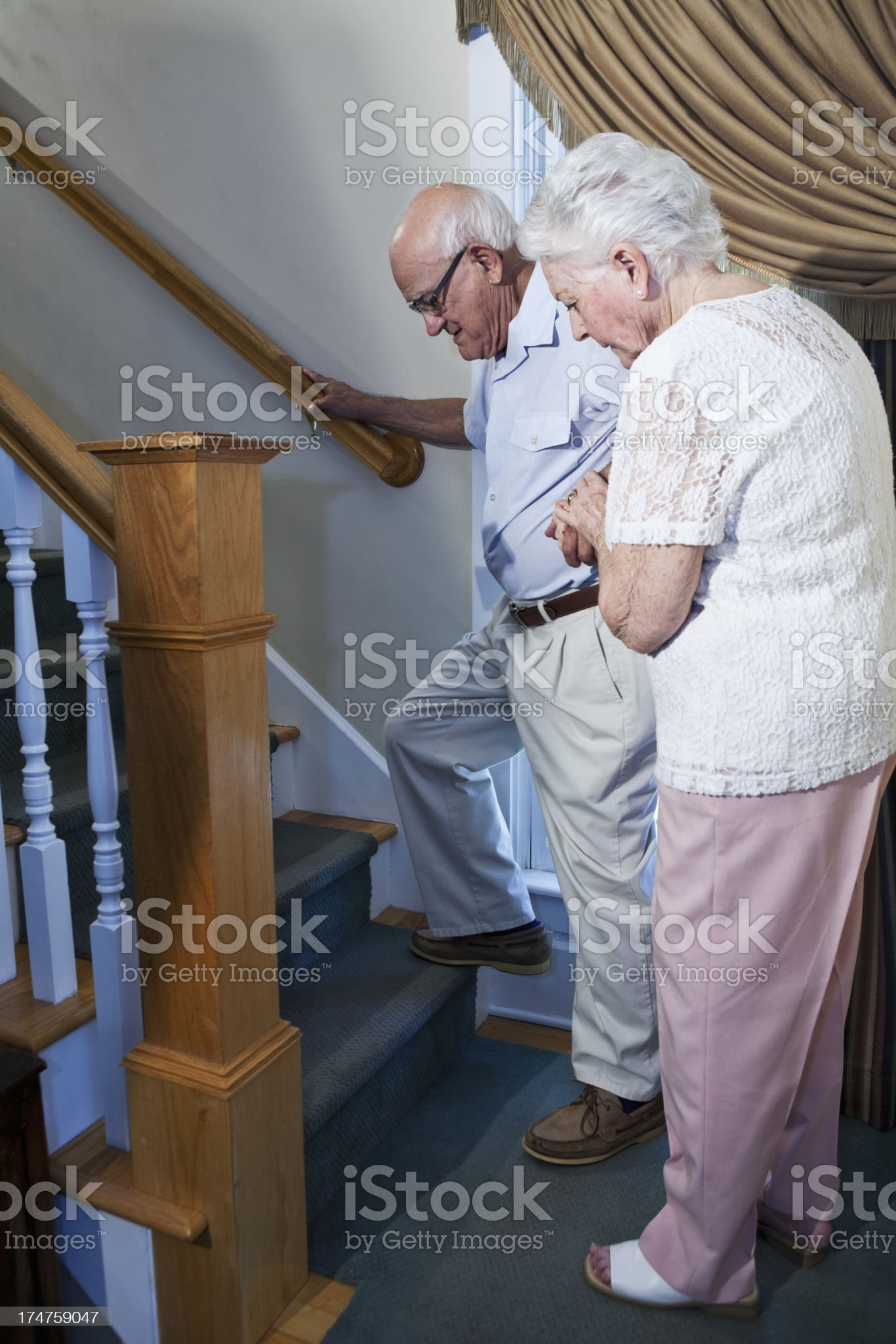 Senior woman helping husband climb staircase royalty-free stock photo