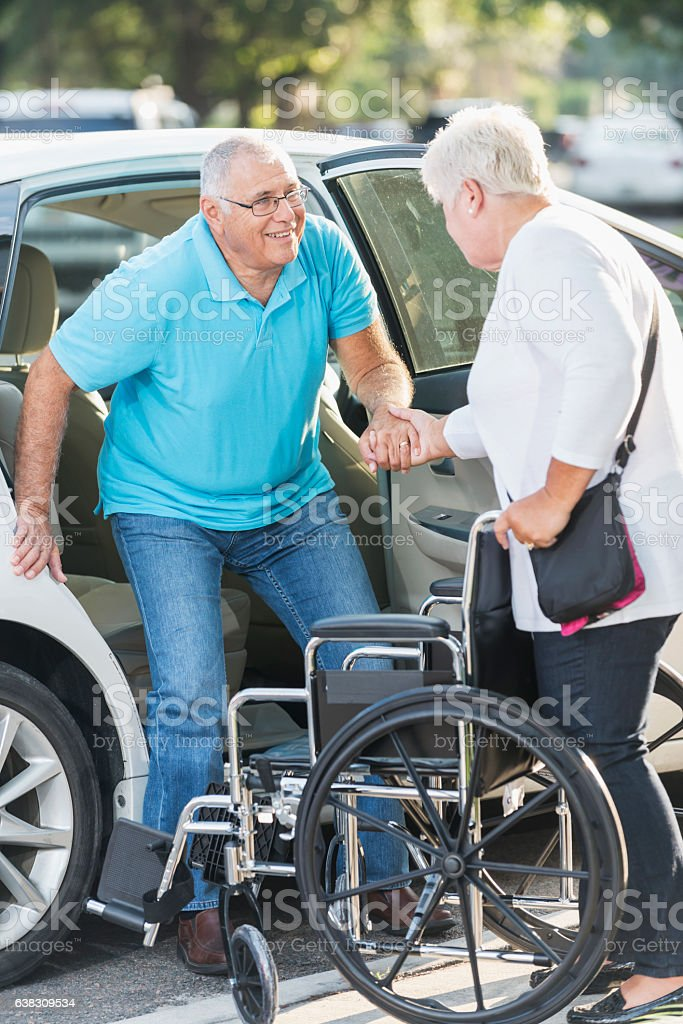 Senior woman helping husband from car to wheelchair stock photo