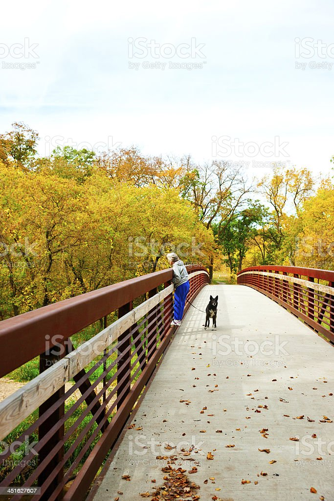 Senior Woman Hiking with Dog on Leash royalty-free stock photo