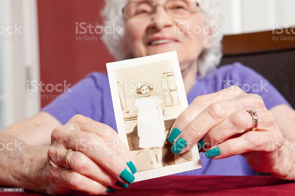 Senior Woman Holding A  Photo From The 30's stock photo