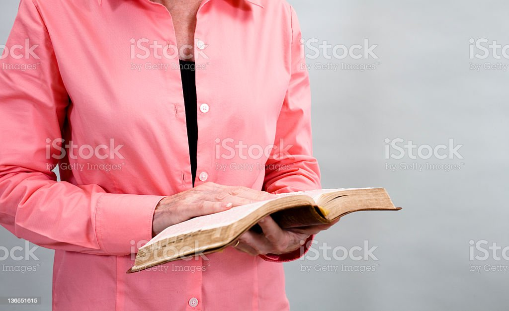 Senior woman holding a worn leather open Bible. royalty-free stock photo
