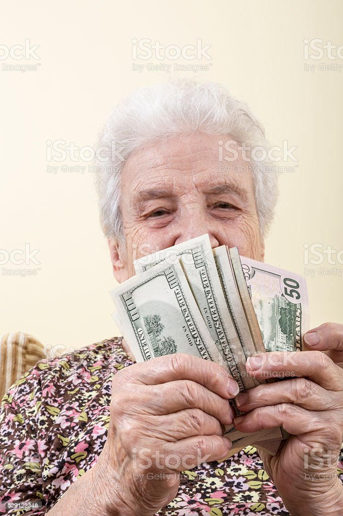 senior woman holding american dollars stock photo