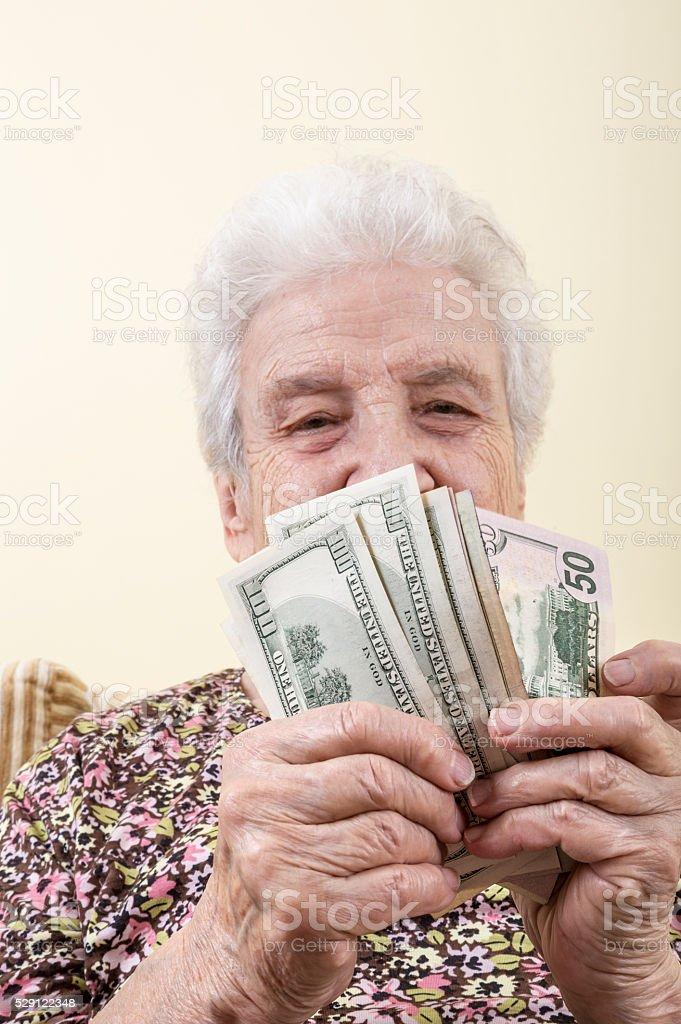 senior woman holding american dollars stock photo