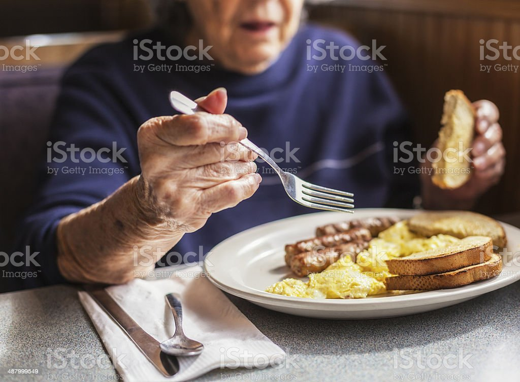 Senior Woman Holding Breakfast Fork stock photo