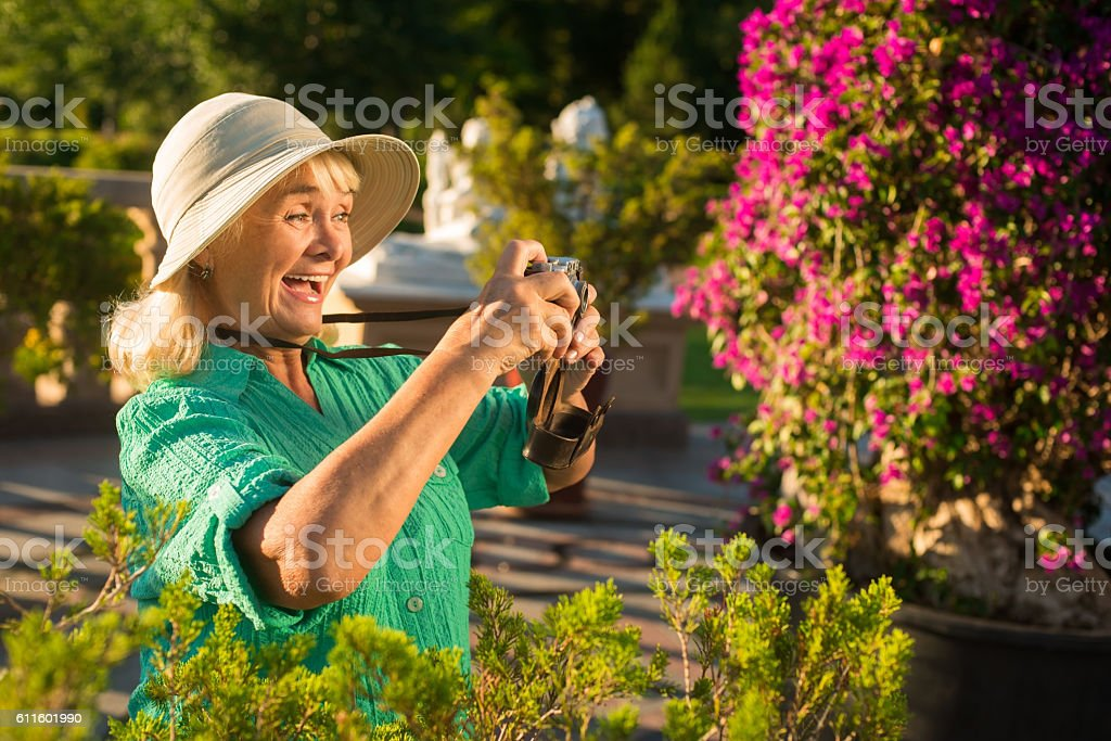 Senior woman holding camera. stock photo