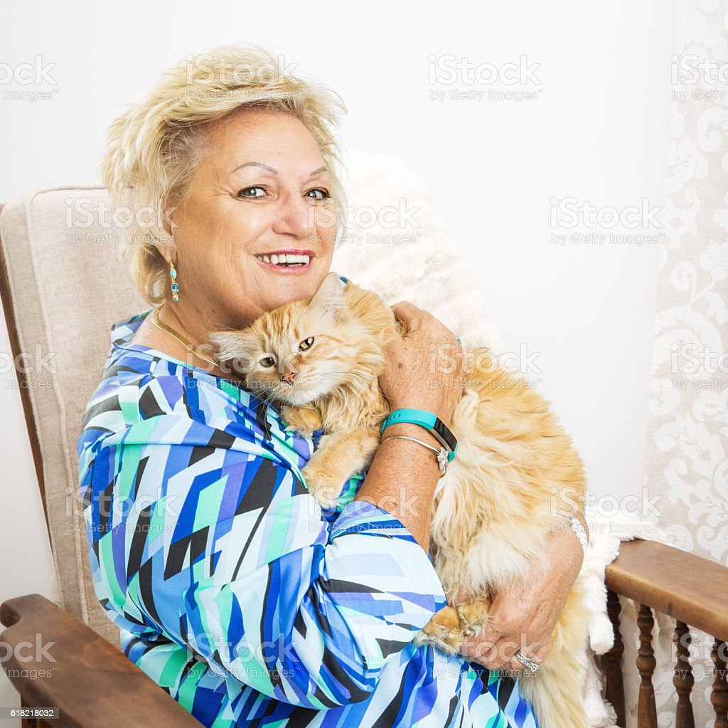 Senior Woman Holding Cat in Chair stock photo