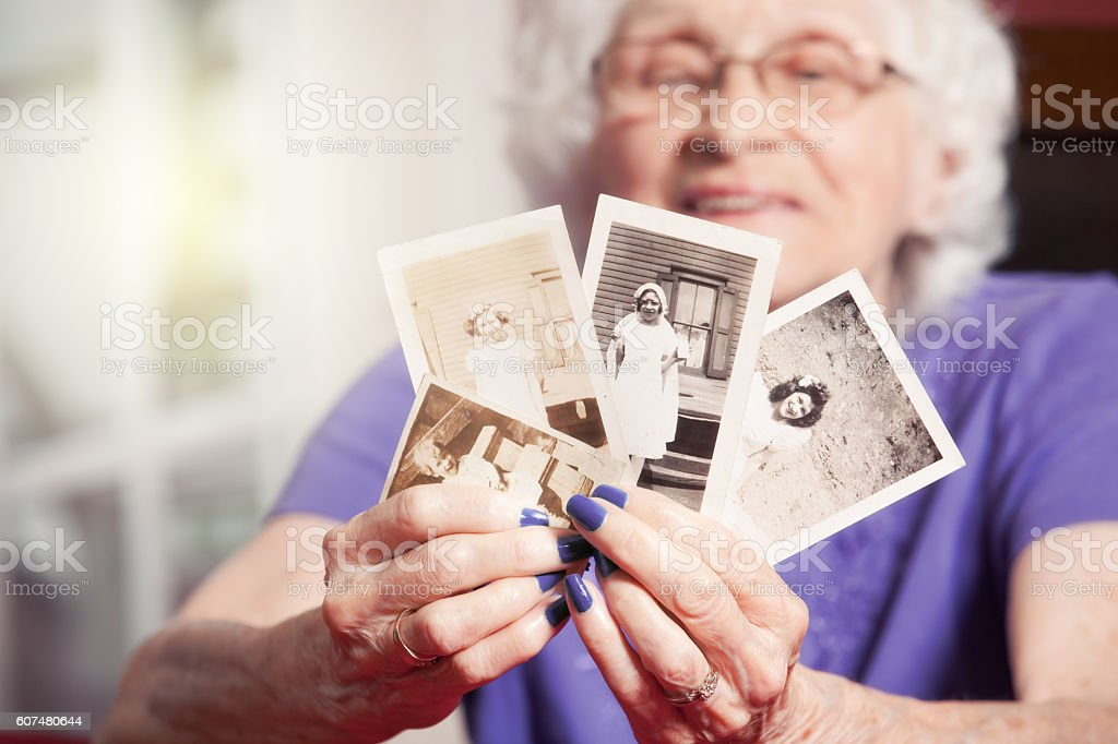 Senior Woman Holding Childhood Photos Of Herself stock photo