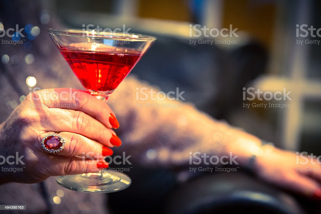 Senior woman holding cocktail New Year's eve party stock photo