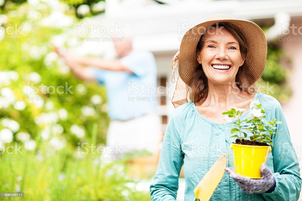Senior Woman Holding Flower Pot And Shovel While Man Gardening stock photo