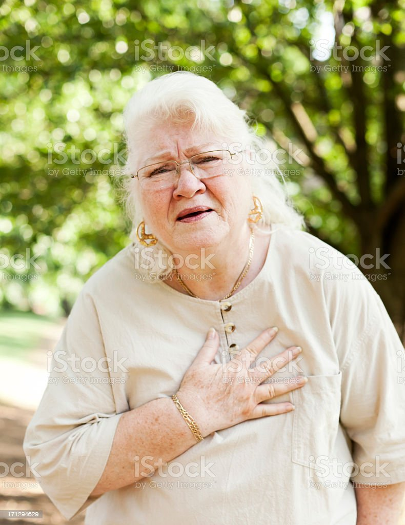 A senior woman holding her chest in pain outside stock photo