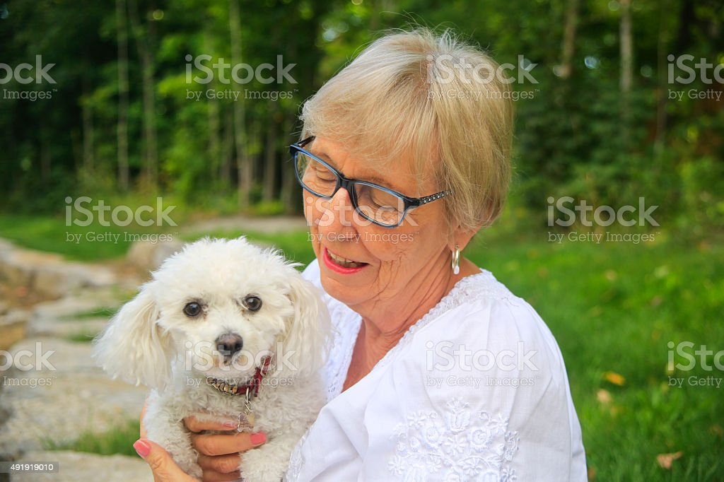 Senior Woman Holding Her Dog stock photo