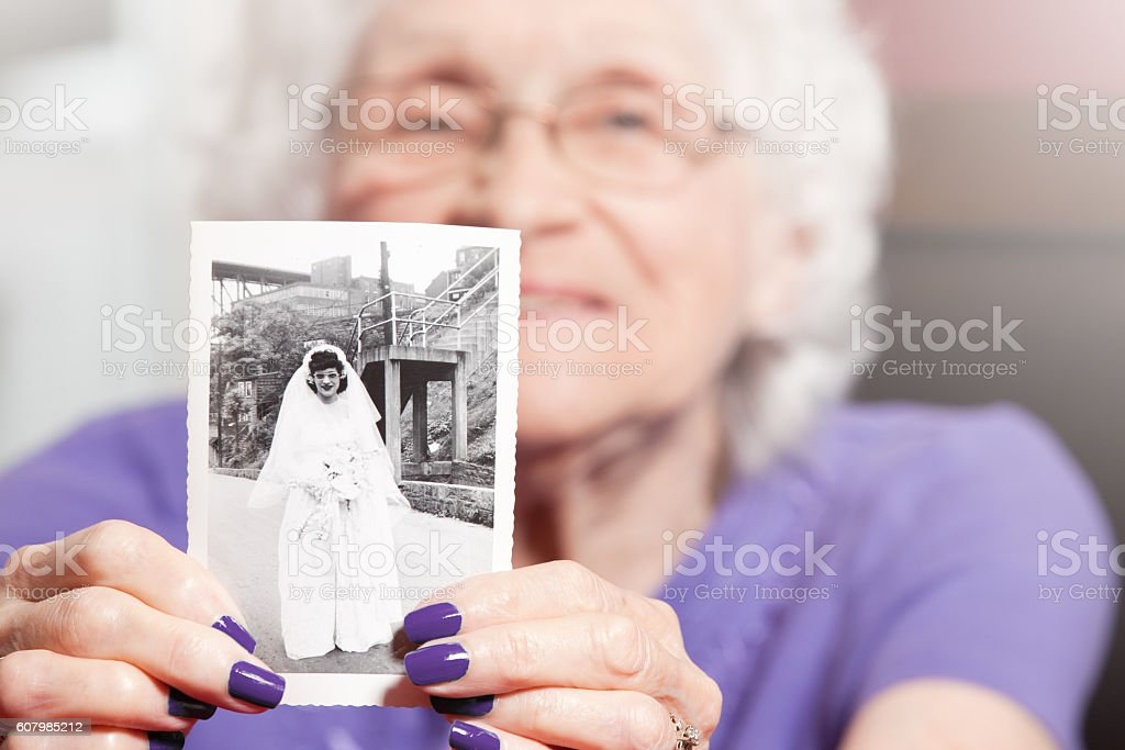 Senior Woman Holding Her Wedding Photo stock photo