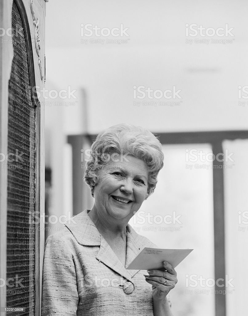Senior woman holding letter, smiling, portrait royalty-free stock photo