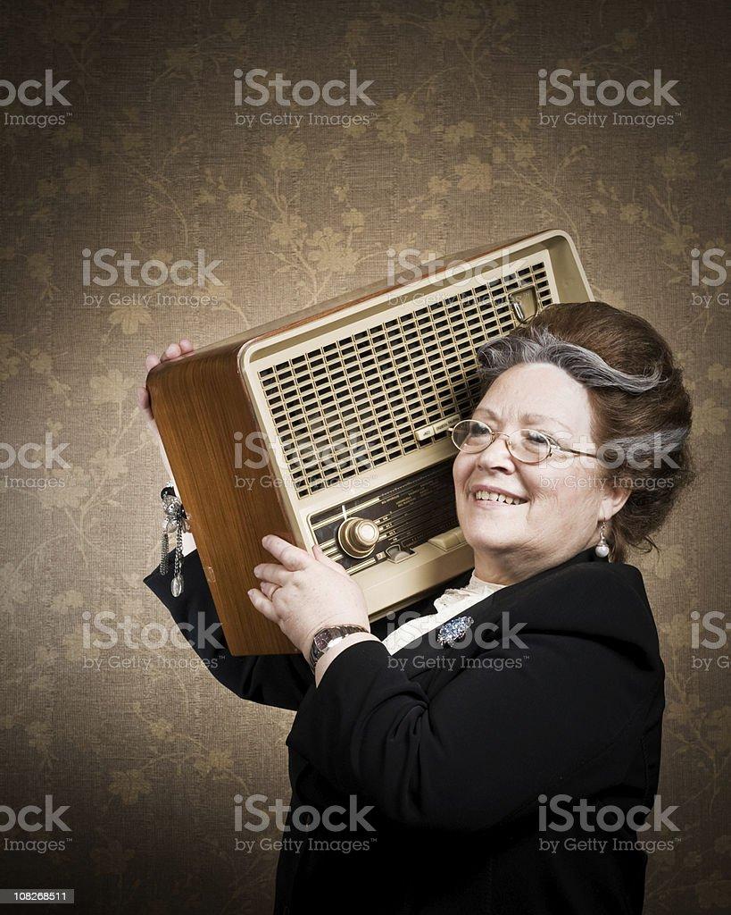 Senior Woman Holding Retro Radio stock photo
