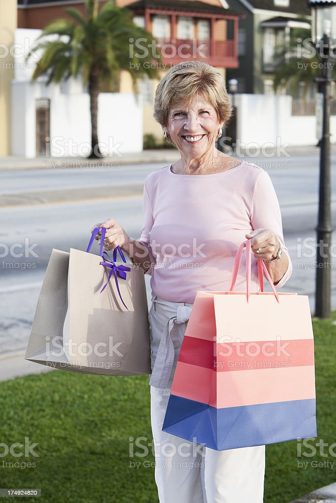 Senior woman holding shopping bags stock photo