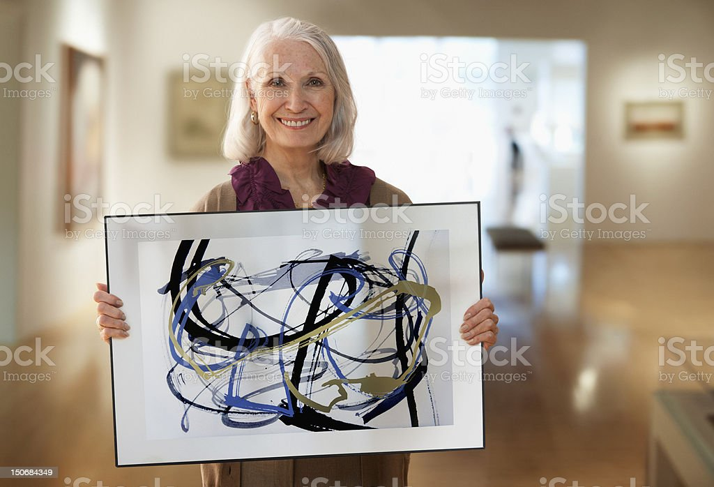 Senior woman holding up designs stock photo
