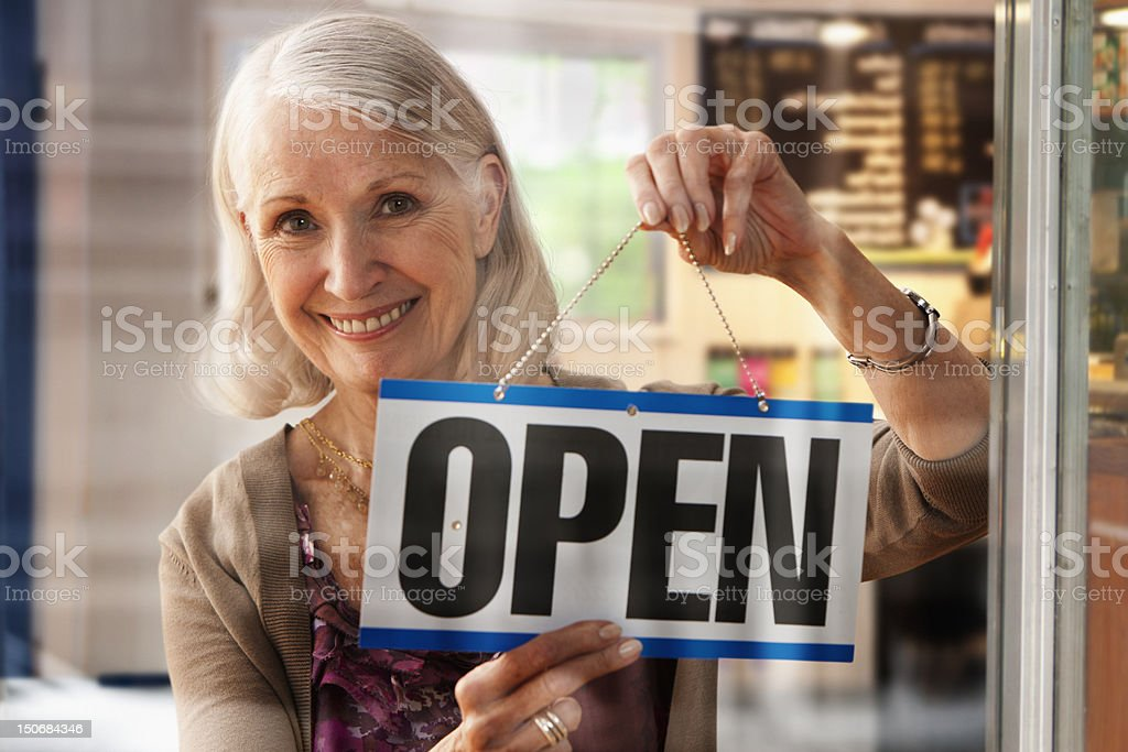 Senior woman holding up open sign royalty-free stock photo