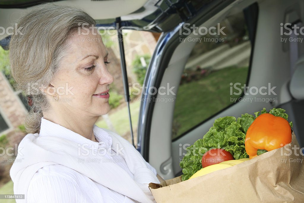 Senior Woman Holding Vegetable Groceries at Trunk of Car royalty-free stock photo