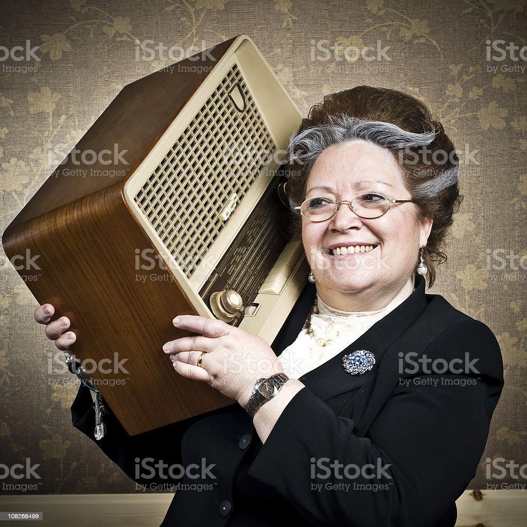 Senior Woman Holding Vintage Radio on Shoulder stock photo