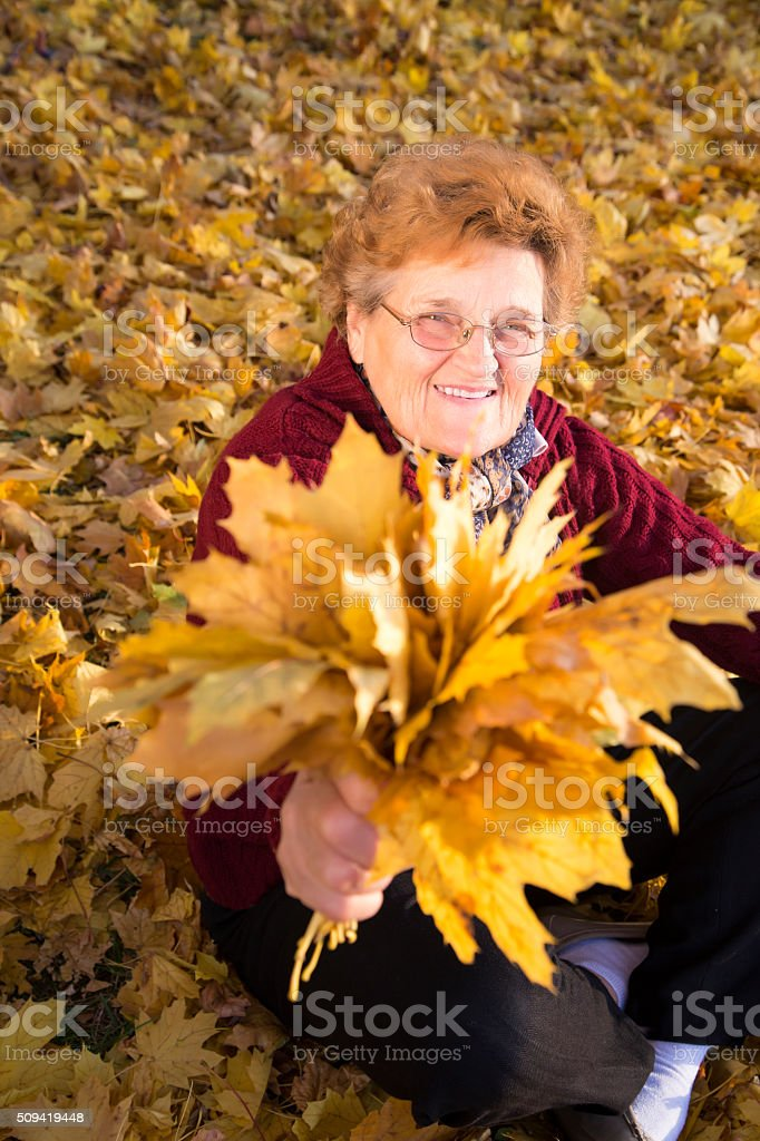 Senior woman holding yellow leaves royalty-free stock photo