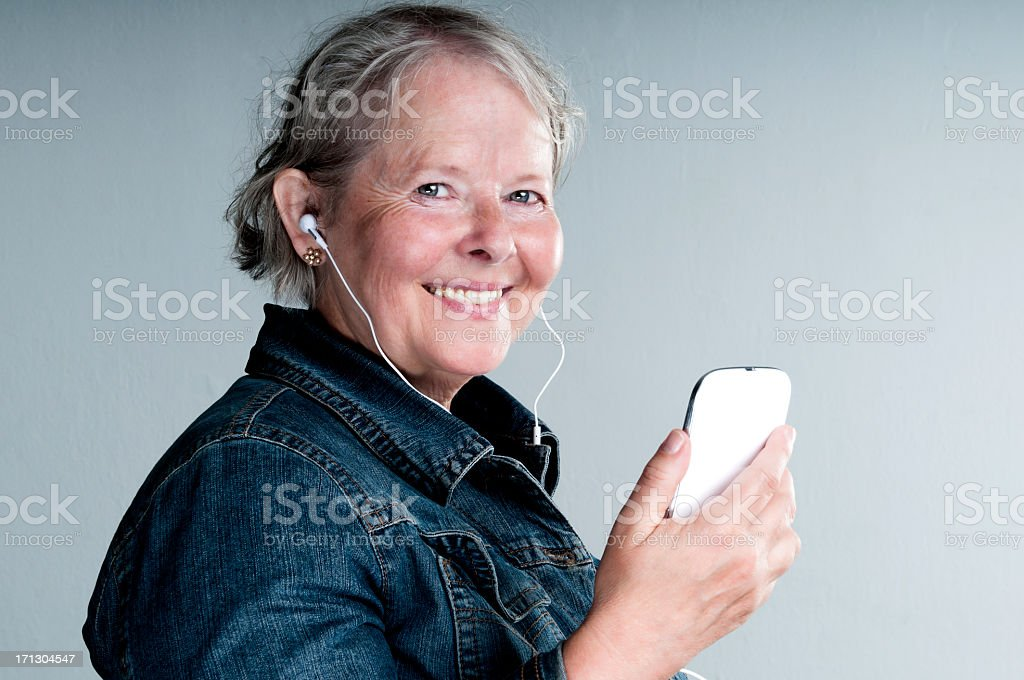 Senior woman holds a smart phone and smiles royalty-free stock photo