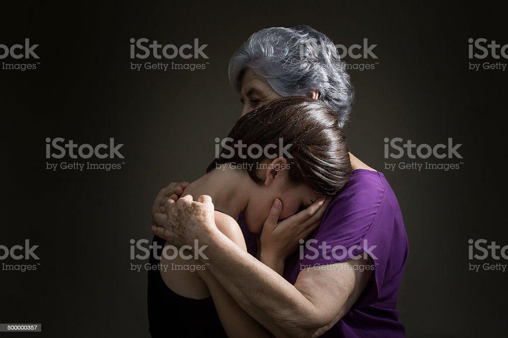 Senior woman hugging granddaughter in grief stock photo