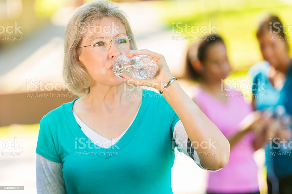 Senior woman hydrates after exercising stock photo