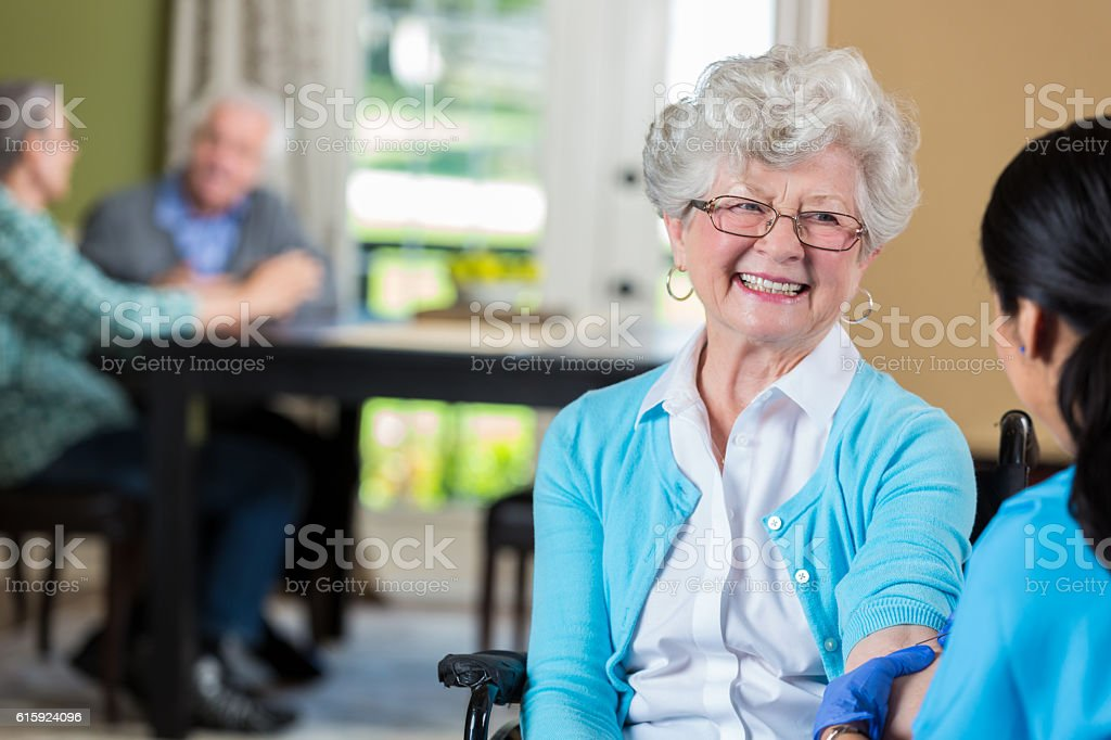 Senior woman in a wheelchair smiles at her nurse stock photo