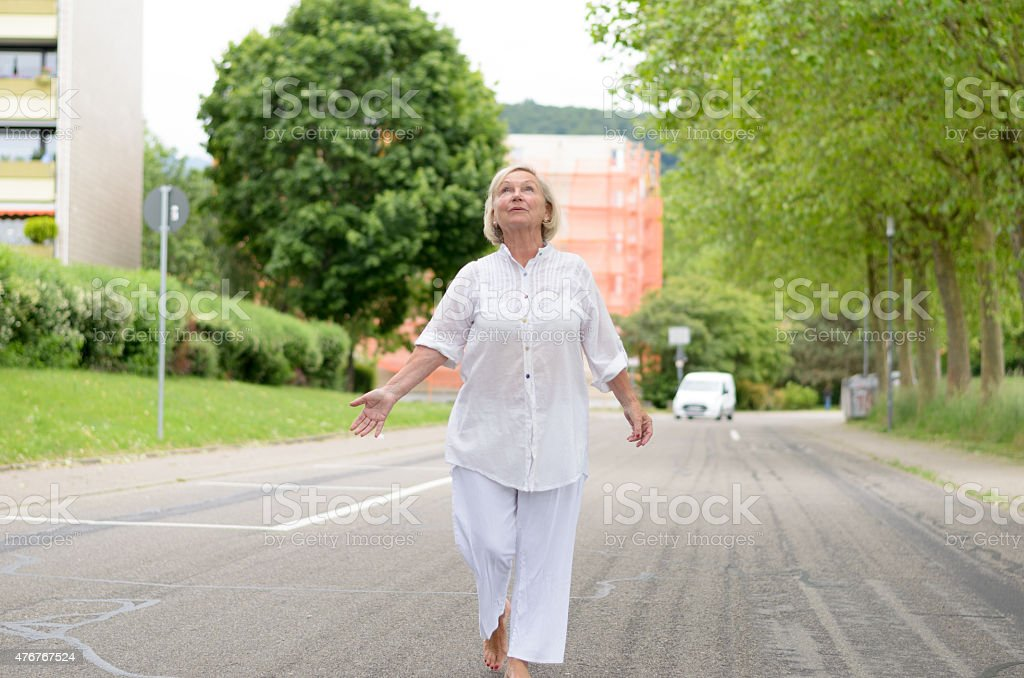 Senior Woman in All White Walking at the Street stock photo