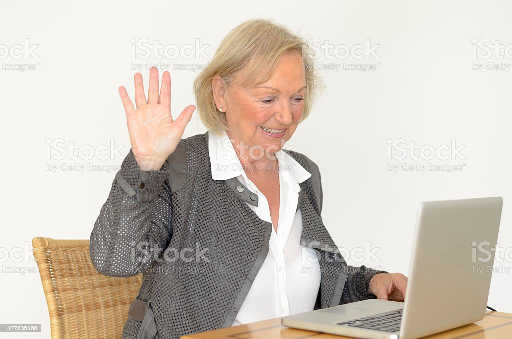 Senior woman in business look in front of a laptop stock photo