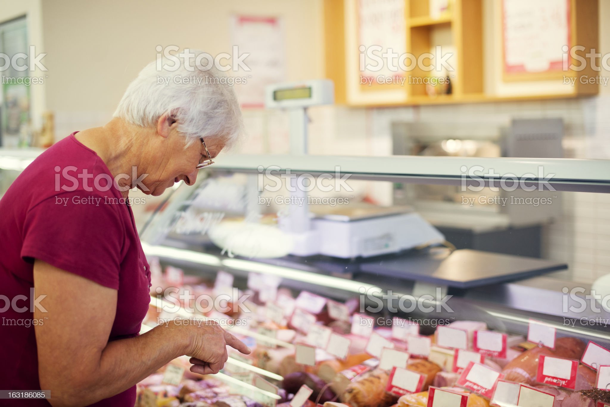 Senior woman in butchers shop royalty-free stock photo