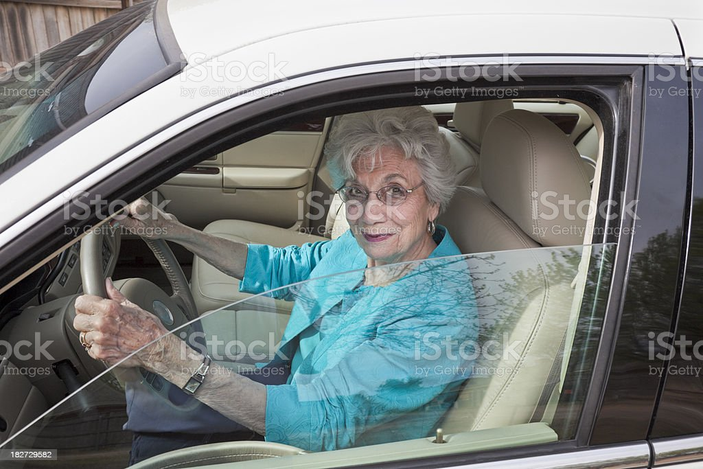 senior woman in car pulling out of garage stock photo