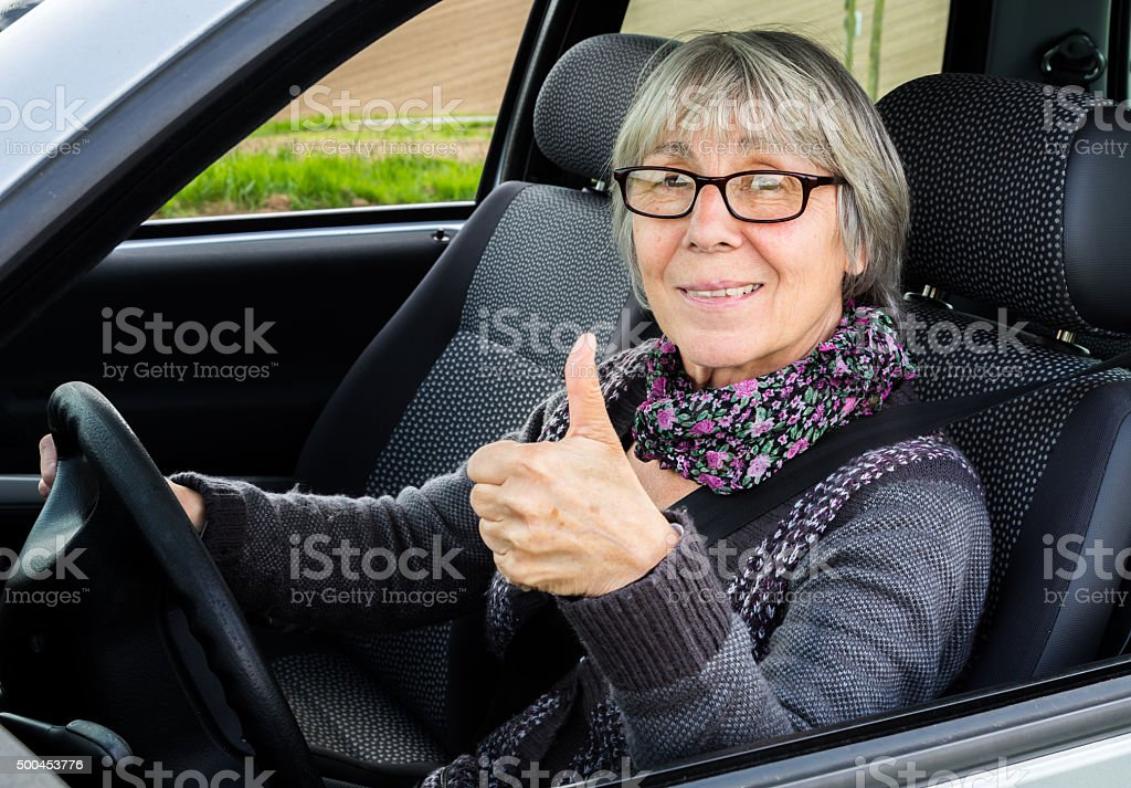 Senior woman in car showing thumbs up stock photo