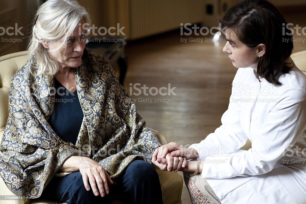 senior woman in care home gets attention from female doctor royalty-free stock photo