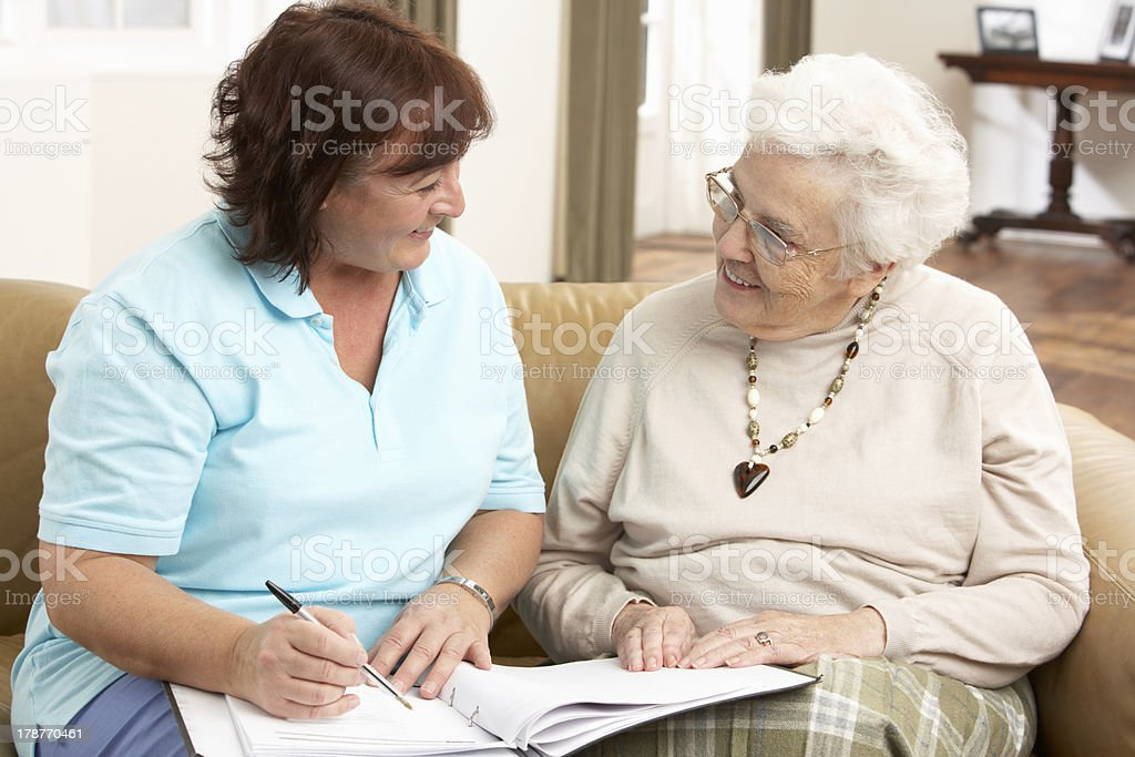 Senior Woman In Discussion With Health Visitor At Home stock photo