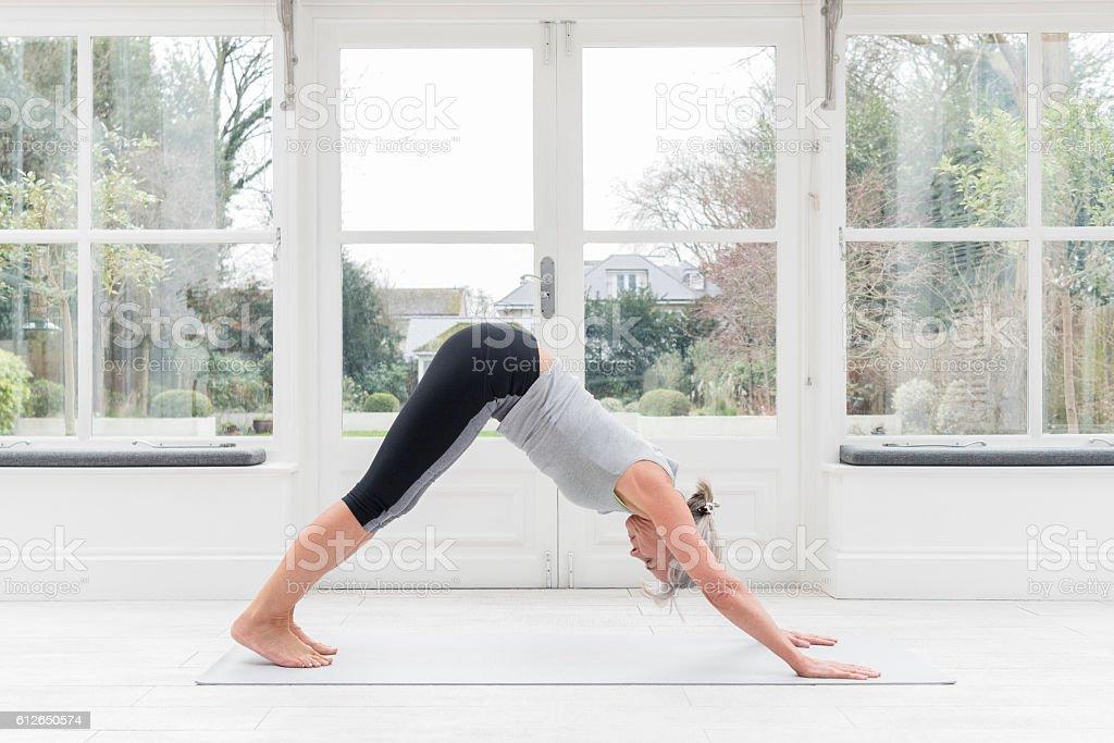 Senior woman in downward dog yoga position stock photo