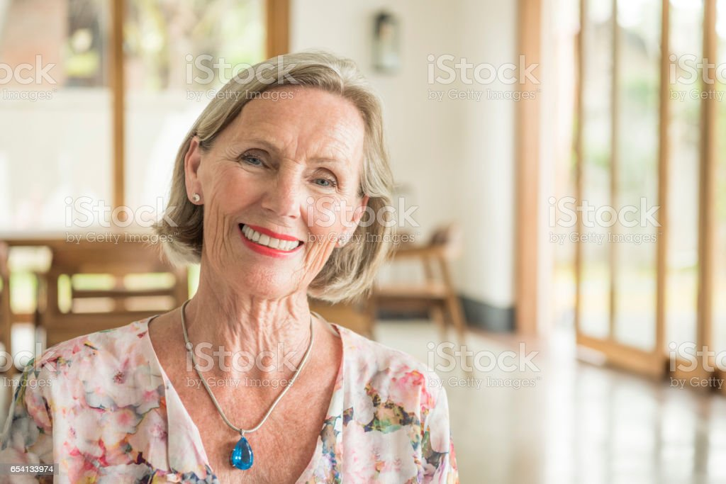 Senior woman in floral blouse, head tilted slightly to one side stock photo