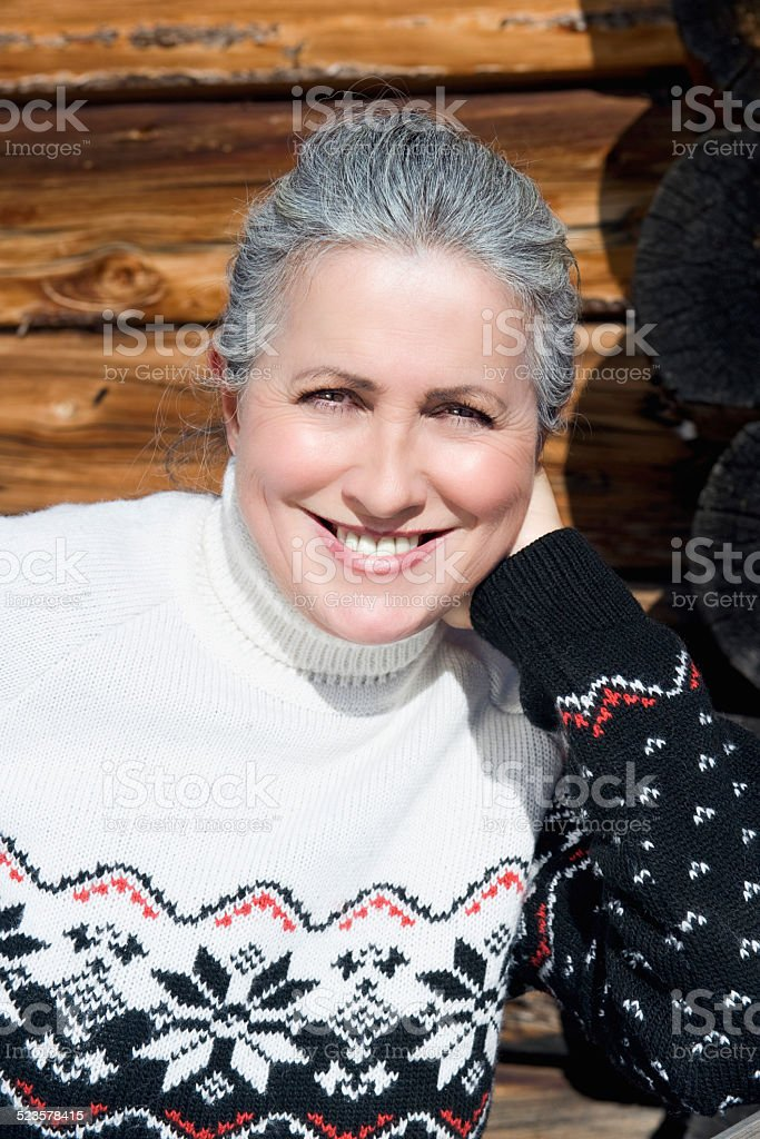 Senior woman in front of wooden wall, smiling, portrait, close-up stock photo