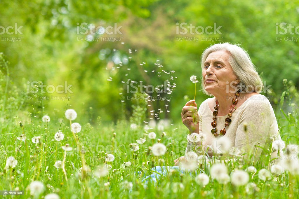 Senior woman in green park stock photo