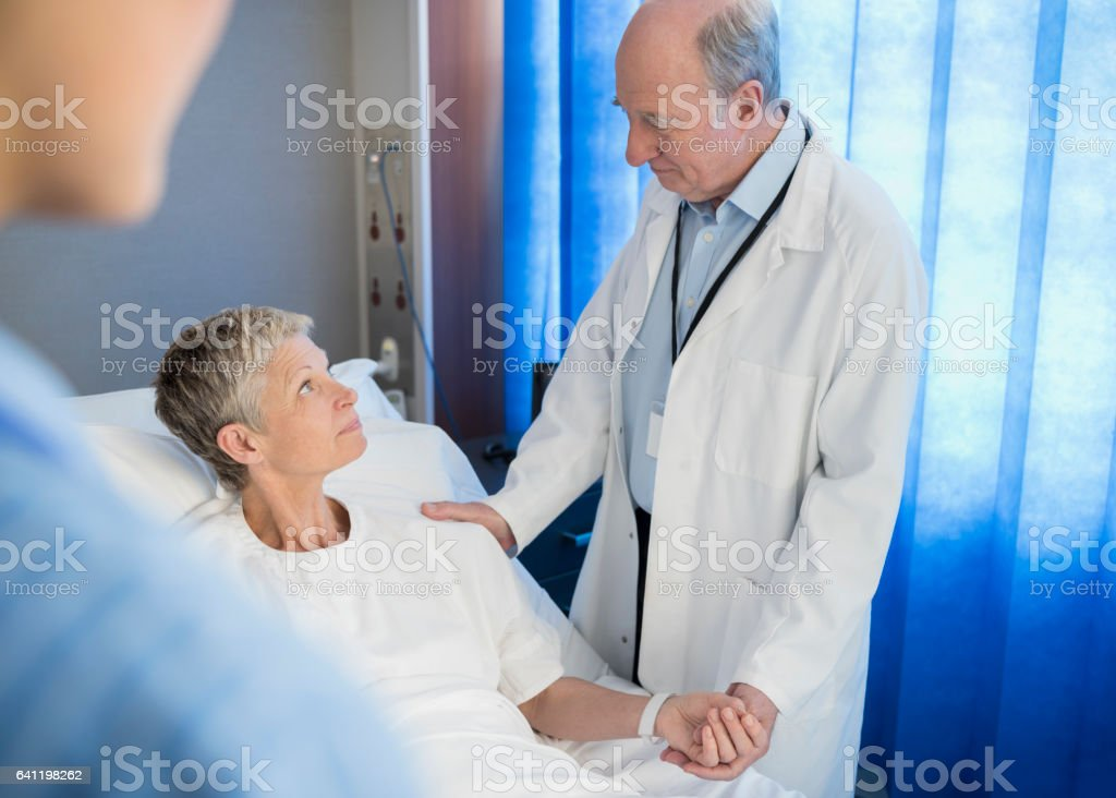 Senior woman in hospital bed, doctor holding her hand stock photo