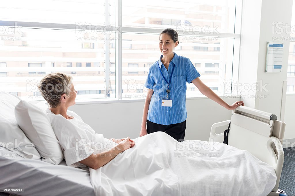 Senior woman in hospital bed talking to Asian nurse, smiling stock photo