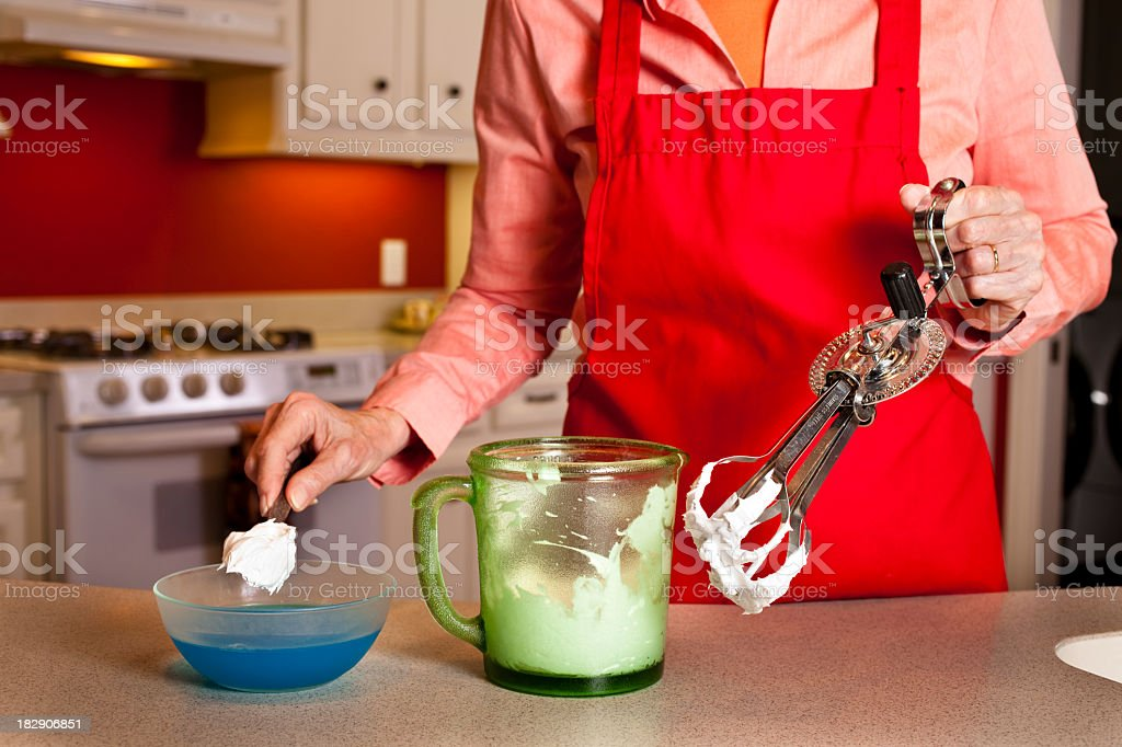 Senior woman in kitchen making whipping cream. royalty-free stock photo